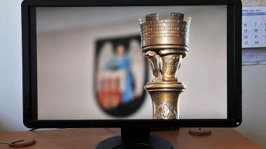 Na zdjęciu: laska przewodniczące i herb Torunia na ekranie komputera