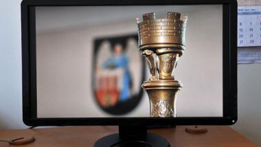 Na monitorze widać laskę przewodniczącego Rady Miasta Torunia, w tle herb miasta