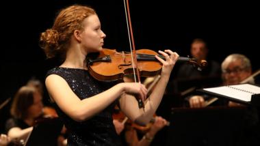 Na zdjęciu młoda solistka gra na skrzypcach podczas koncertu