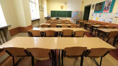 Na zdjęciu widać salę klasową, puste ławki i krzesła, z przodu na ścianie wisi tablica