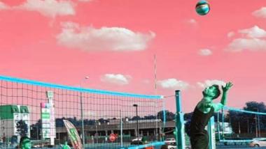 Na zdjęciu: mężczyzna na boisku do siatkówki plażowej odbijający piłkę