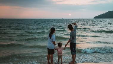 Na zdjęciu rodzina z dzieckiem stoi na plaży na tle morza