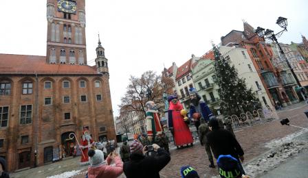 Figury trzech króli stoją na Rynku Staromiejskim, w tle Ratusz