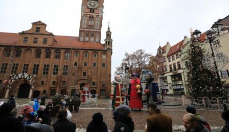 Figury trzech króli stoją na Rynku Staromiejskim, w tle ratusz staromiejski