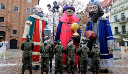Figury trzech króli stoją na Rynku Staromiejskim, przed nimi żołnierze pozują do zdjęcia